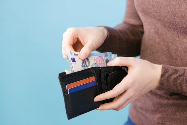 Eine frau nimmt geld aus einer brieftasche auf einem blauen hintergrund mit einem platz für text heraus. zahlungskonzept.
