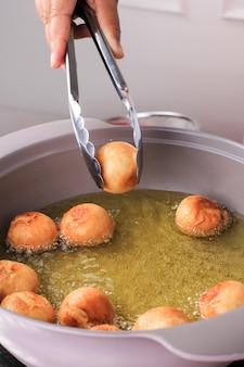 Eine frau nimmt mini-donut aus heißem öl mit einer rostfreien zange auf.