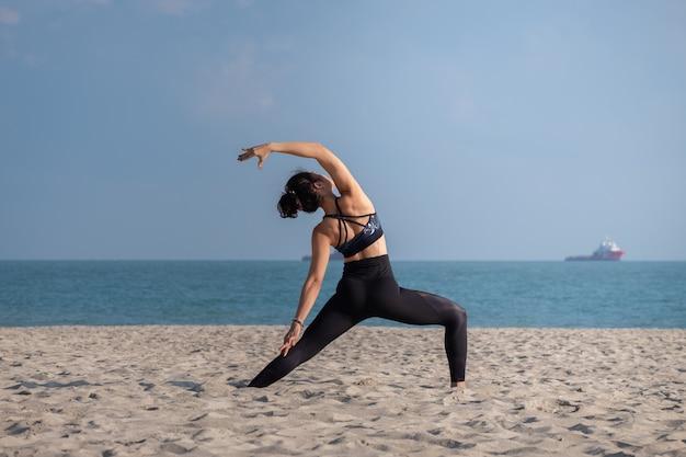 Eine frau praktizieren yoga am strand