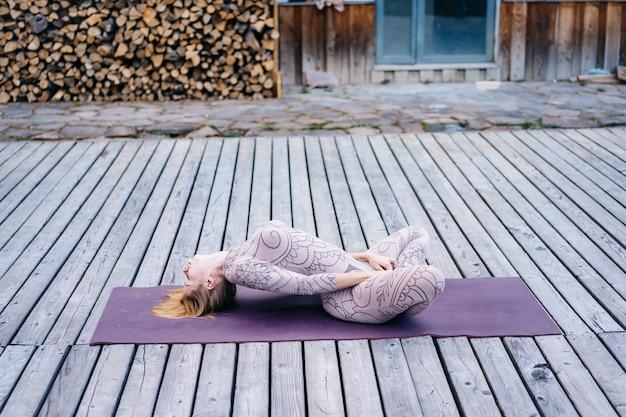 Eine frau praktiziert morgens yoga auf einer terrasse an der frischen luft.