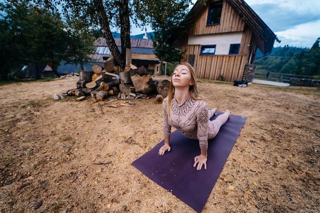 Eine frau praktiziert morgens yoga in einem park an der frischen luft.