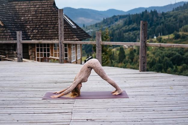 Eine frau praktiziert yoga am morgen auf einer terrasse an der frischen luft.