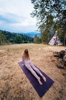 Eine frau praktiziert yoga am morgen in einem park an der frischen luft.