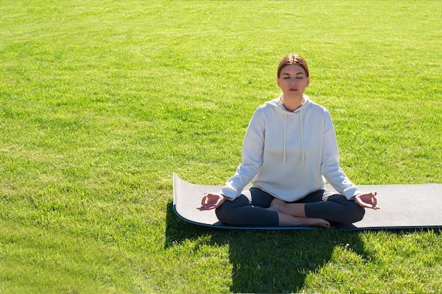 Eine frau praktiziert yoga im freien auf dem rasen. speicherplatz kopieren