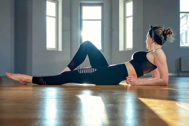 Eine frau praktiziert yoga in einem fitnessraum im morgengrauen