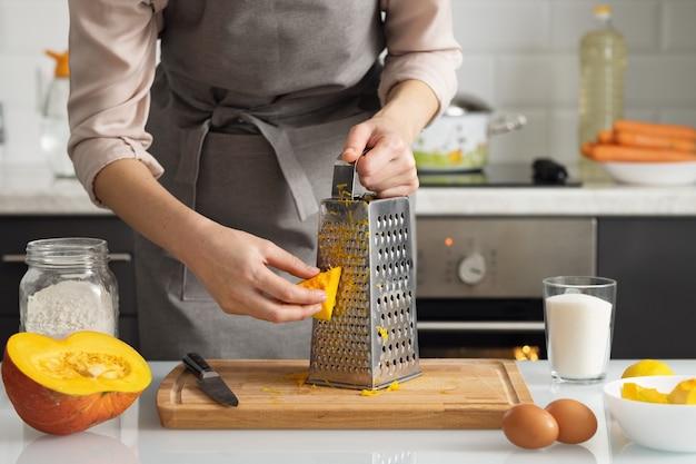 Eine frau reibt einen kürbis, um einen kuchen zu backen