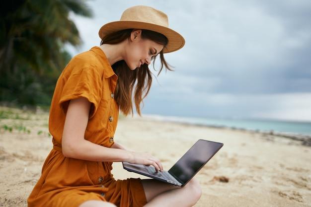 Eine frau reist mit einem laptop entlang des ozeans entlang des sandes mit palmen