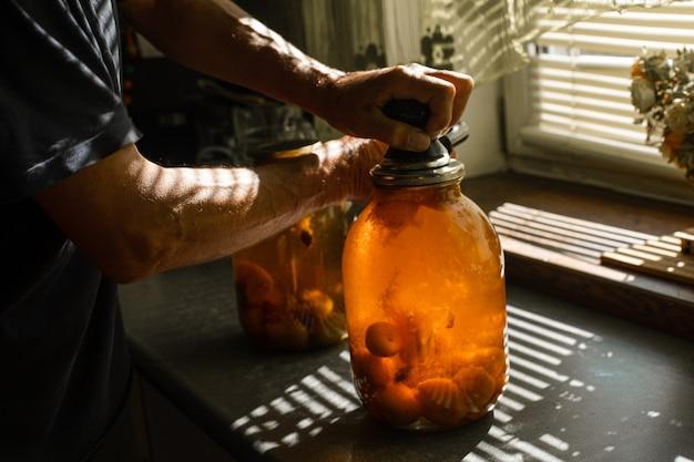 Eine frau rollt im sommer zu hause im dorf ein kompott in einem großen glas unter der sonne