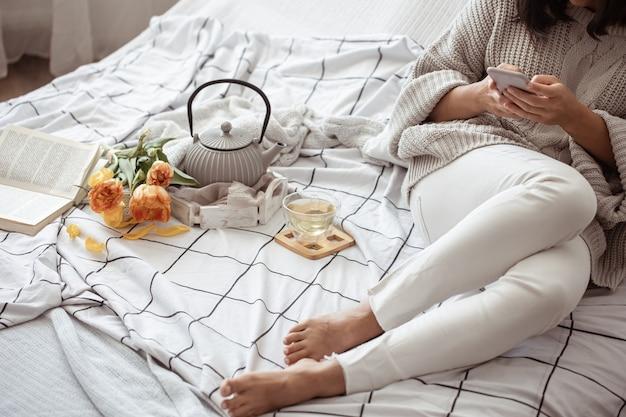 Eine frau ruht sich mit tee, einem buch und einem strauß tulpen im bett aus. frühlingsmorgen- und wochenendkonzept.