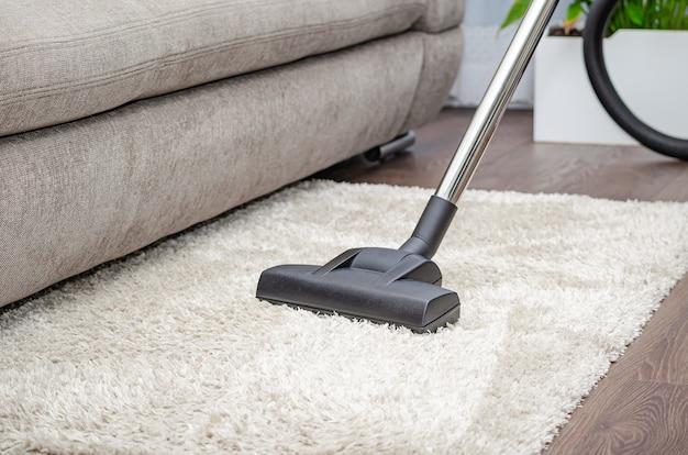 Eine frau saugt mit einem staubsauger einen grauen teppich. reinigungs- und sauberkeitskonzept.