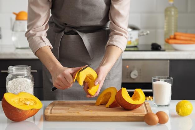Eine frau schält einen kürbis, um einen kuchen zu backen