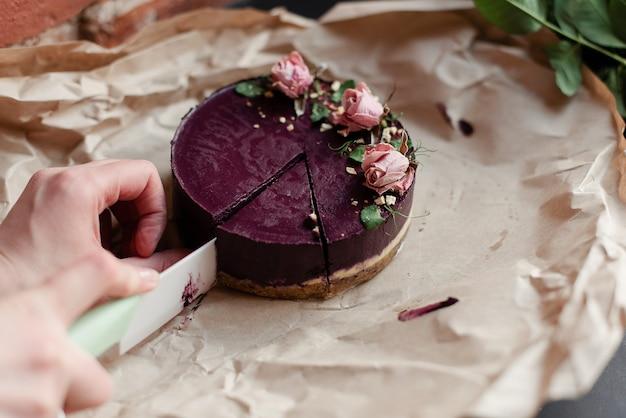 Eine frau schneidet einen kuchen mit einem messer. schneiden sie ein stück kuchen. köstlicher natürlicher kuchen. schönes dessert mit dekor. ein natürliches dessert.
