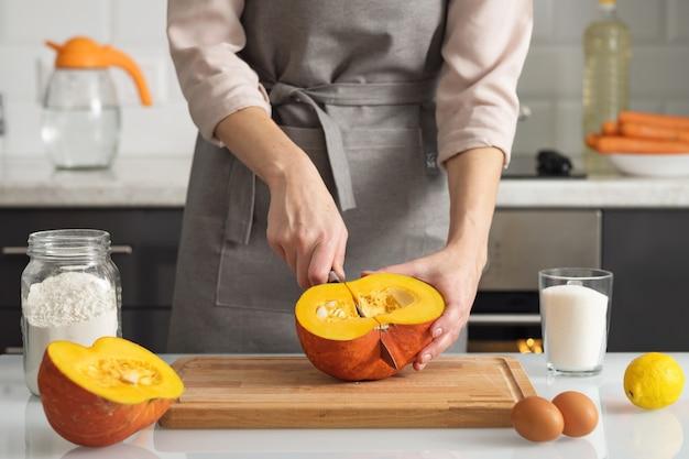 Eine frau schneidet einen kürbis, um in ihrer küche einen kuchen zu backen