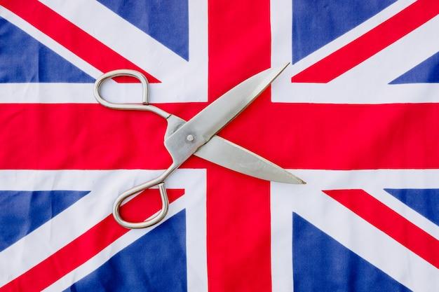 Eine frau schneidet mit einer schere die britische flagge aus protest.