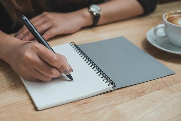 Eine frau schreibt auf ein notizbuch und eine kaffeetasse auf einen holztisch