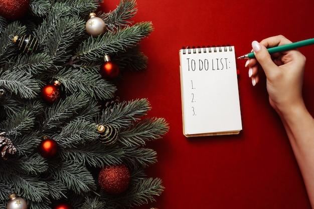 Eine frau schreibt eine einkaufs- oder aufgabenliste in ein notizbuch auf rotem grund neben weihnachtsbaumzweigen und -dekorationen.