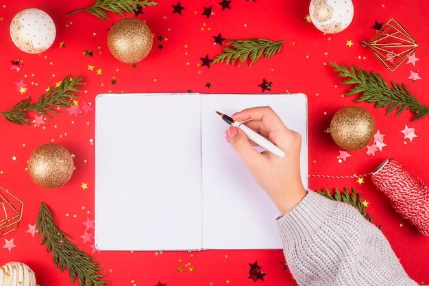 Eine frau schreibt in ein notizbuch eine elternliste oder einen plan unter dekorationen auf rot.