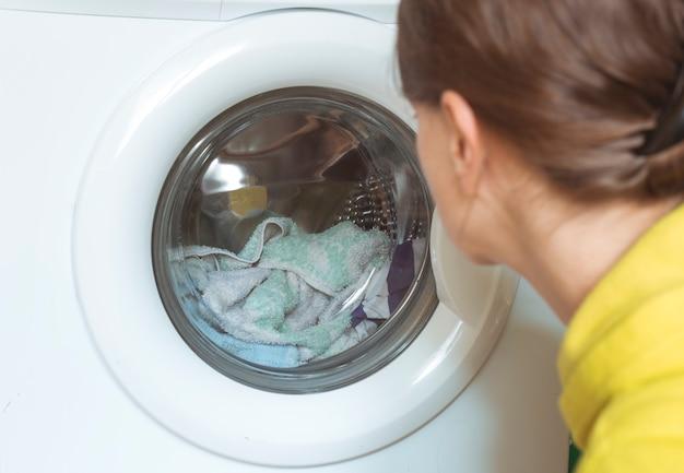 Eine frau sieht, wie eine waschmaschine funktioniert.