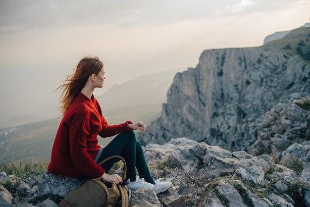 Eine frau sitzt am rand einer klippe, ein touristenreisender schaut auf den sonnenuntergang