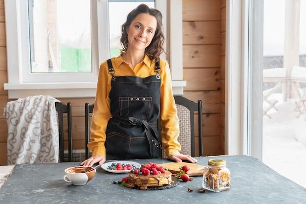 Eine frau sitzt am tisch mit einem kuchen aus pfannkuchen und beeren für einen feiertag