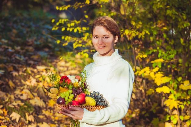 Eine frau sitzt auf dem mit herbstlaub bedeckten boden und hält einen herbstkorb mit früchten und blumen