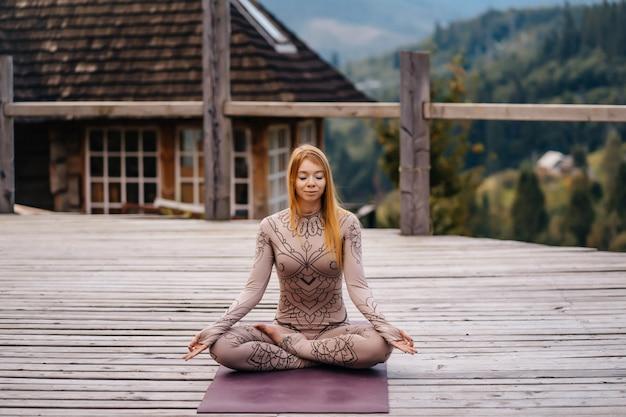 Eine frau sitzt im lotussitz am morgen an der frischen luft.