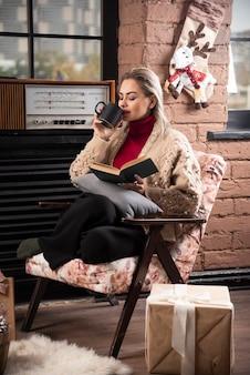 Eine frau sitzt und liest buch und trinkt kaffee