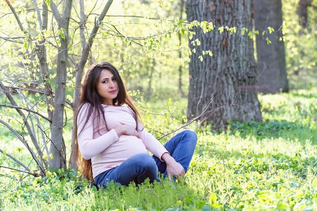 Eine frau sitzt unter einem frühlingsbaum