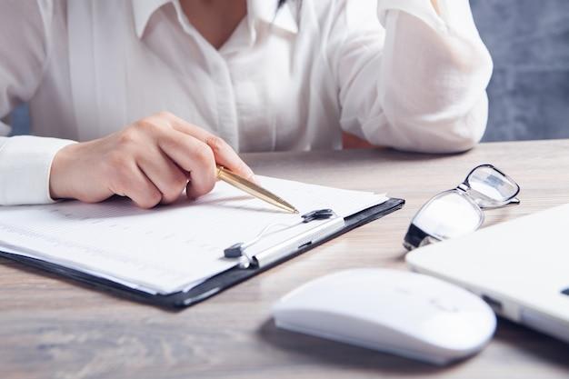 Eine frau sitzt vor einem laptop und studiert dokumente