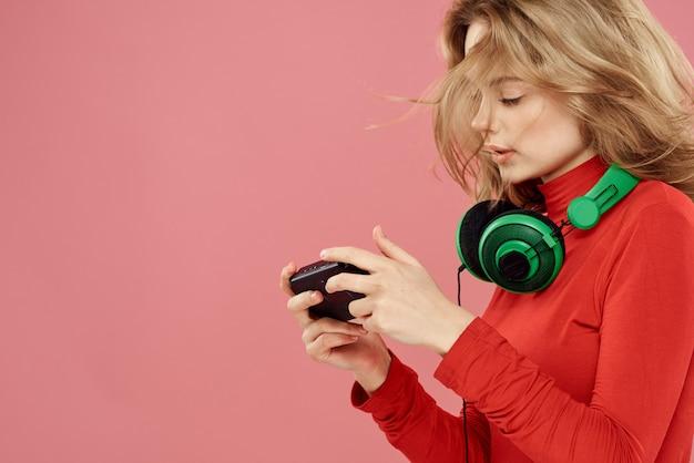 Eine frau spielt ein computerspiel in konsolen mit joysticks in kopfhörern