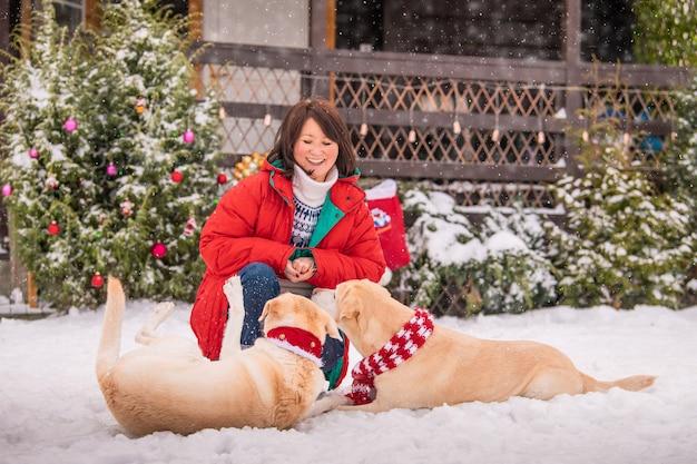 Eine frau spielt mit labradorsmi-hunden in der nähe eines geschmückten weihnachtsbaums während eines schneefalls im winter im innenhof eines mehrfamilienhauses.