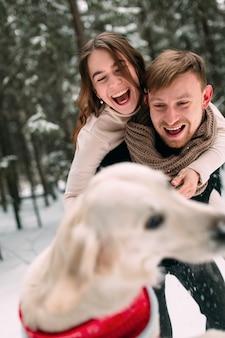 Eine frau sprang einem mann in einem verschneiten wald auf den rücken und sie haben spaß