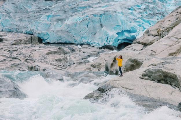 Eine frau steht auf dem nygardsbreen-gletscher und dem gletscherfluss in norwegen.