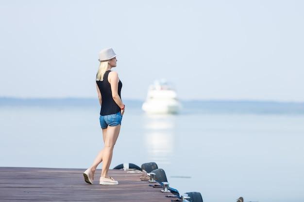Eine frau steht auf einem pier, eine yacht segelt in der nähe