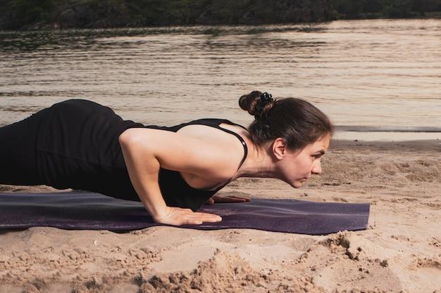 Eine frau steht in einer plankenpose am flussufer am strand bei sonnenuntergang im sommer. yoga- oder fitnesskurse in der natur.