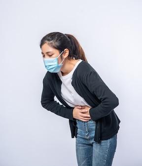 Eine frau steht mit bauchschmerzen und drückt ihre hand auf ihren bauch.