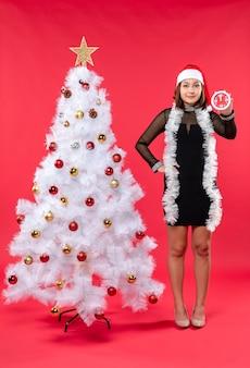 Eine frau steht neben dem weihnachtsbaum