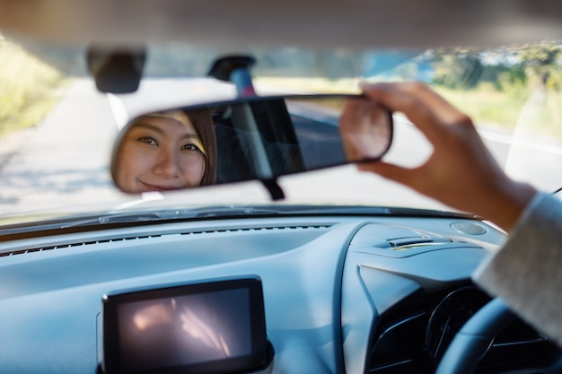 Eine frau stellt beim autofahren einen rückspiegel ein