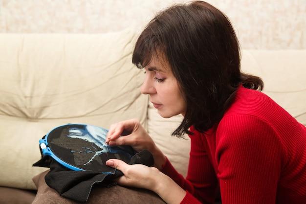 Eine frau stickt ein bild mit fäden in einem kreuz, während sie auf dem sofa liegt.