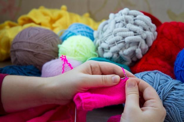 Eine frau strickt auf stricknadeln einen rosa pullover