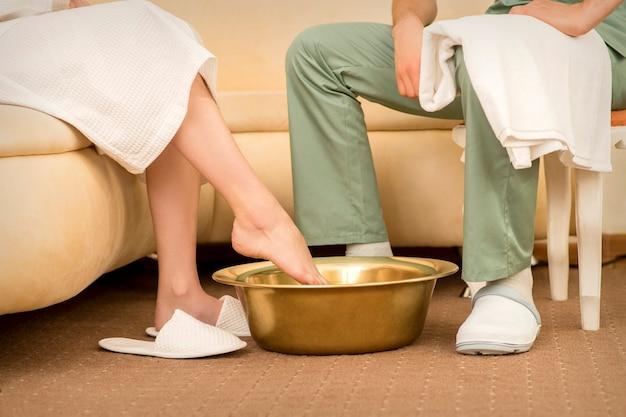 Eine frau taucht die füße in eine schüssel, bevor sie die fußtherapie wäscht
