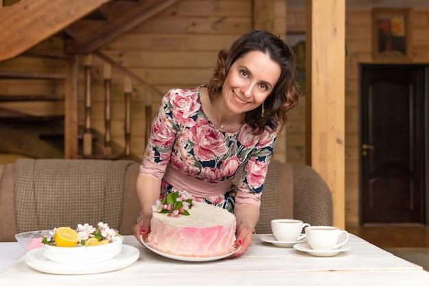 Eine frau trägt einen leckeren kuchen zum festlichen tisch