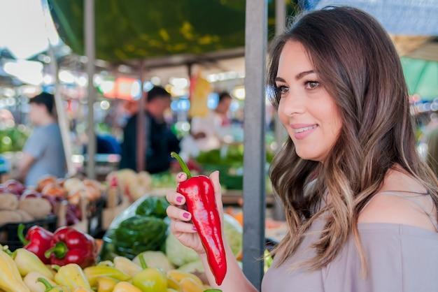 Eine frau trägt paprika in den händen. frau, die frisches gemüse zum messen im lebensmittelgeschäft wählt