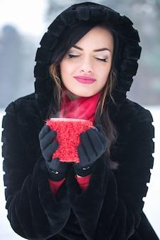 Eine frau trinkt im winter ein heißes getränk aus einer tasse