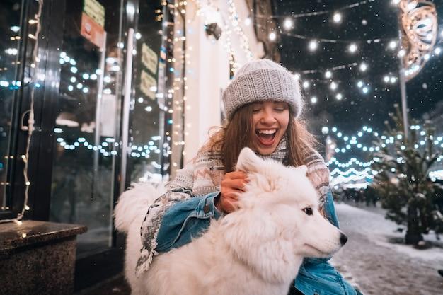 Eine frau umarmt ihren hund auf einer nachtstraße.