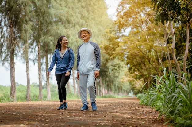 Eine frau und ein großvater gehen joggen auf der straße im park großvater reden