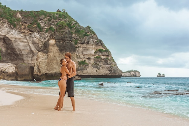 Eine frau und ein mann gehen am diamond beach auf der insel nusa penida entlang