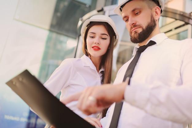 Eine frau und ein mann in businesskleidung und in weißen bauhelmen besprechen einen bauplan