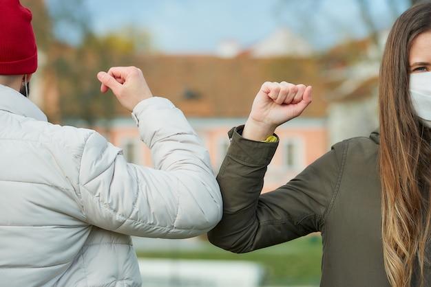 Eine frau und ein mann mit gesichtsmasken stoßen an die ellbogen, anstatt sie mit einem handschlag zu begrüßen