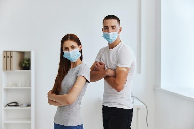 Eine frau und ein mann mit medizinischen masken bei einem krankenhaustermin und einer spritze gegen